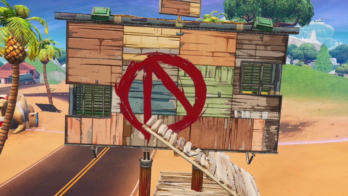 رسم رمز Vault باللون الأحمر على ظهر لوحة إعلانية في منطقة Pandora Fortniteخريطة