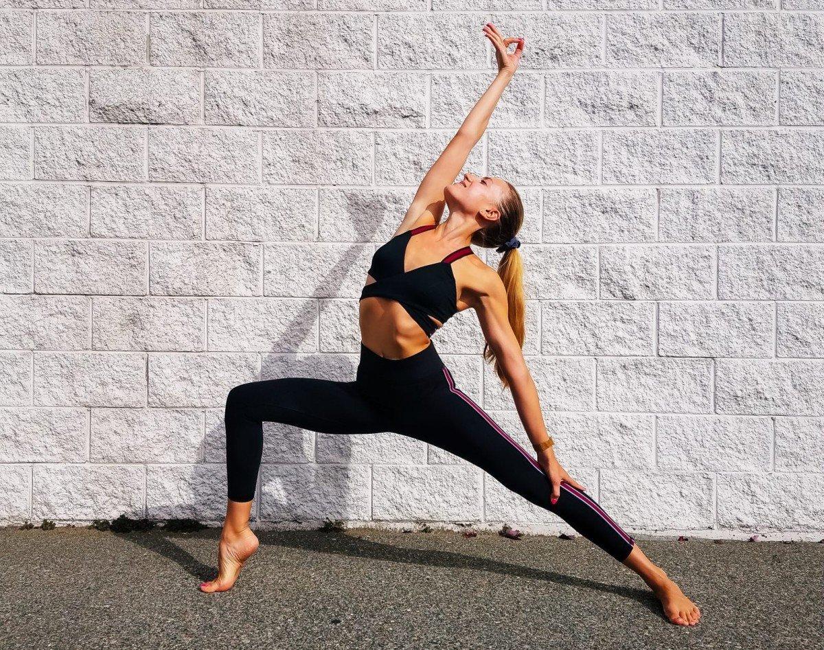امرأة تمارس رياضة اليوغا المحارب العكسي أمام جدار من الطوب الأبيض
