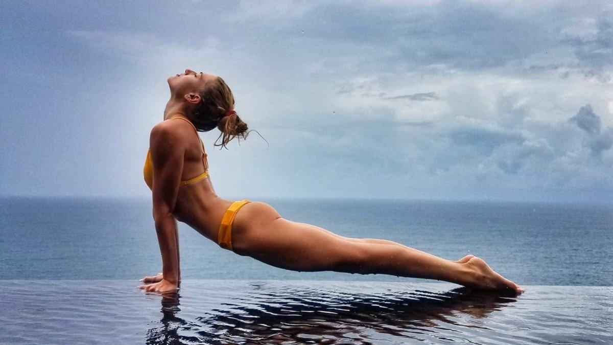 المرأة التي تمارس رياضة اليوغا التي تواجه الكلب تصعد على حافة حمام سباحة لا متناهي