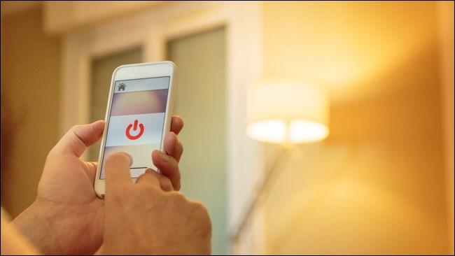 يد باستخدام وحدة التحكم في الإضاءة الذكية على الهاتف الذكي.